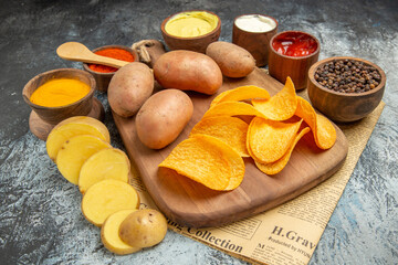 Side view of homemade delicious potato chips on wooden cutting board different spices and flavors on newspaper on gray table