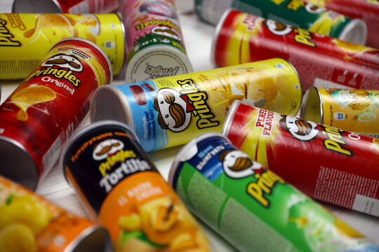 Pringles variety of flavors. Many cardboard tube cans with Pringles potato chips. Pringles is a brand of potato snack chips owned by the Kellogg Company