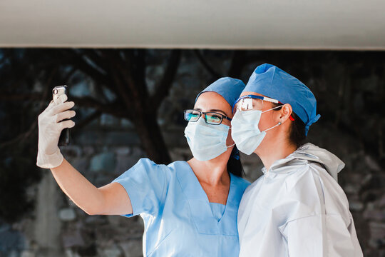 couple of latin women doctors taking a photo selfie with a smartphone in a Mexican hospital in Mexico or Latin America
