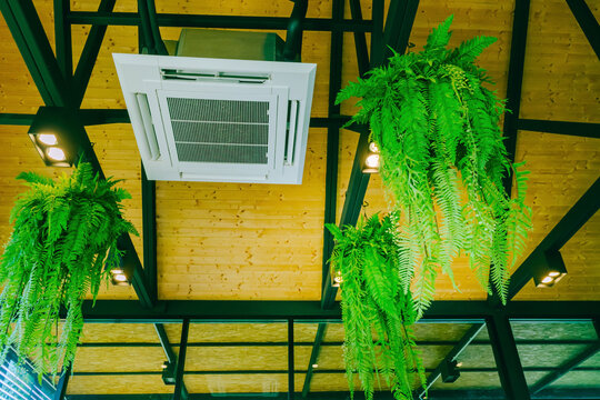 Ceiling air conditioning system, open-air, circulating air throughout the modern style, popular installed in coffee shops. Ceiling mounted cassette type air conditioner in the cafes.