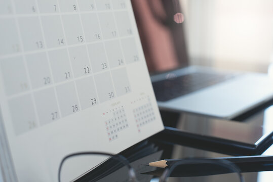 Closeup of calendar and laptop computer and mobile phone on table in office with nobody