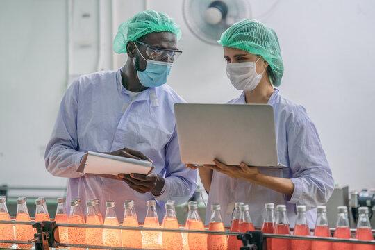 production line supervisor and worker work together in beverage production line