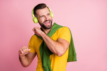 Photo of attractive positive young man dance wear headphones music lover isolated on pastel pink color background