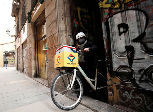 Geraldine Caillaud, member of the bicycle delivery company Les Mercedes, leaves their office with a bicycle at Barcelona's city center