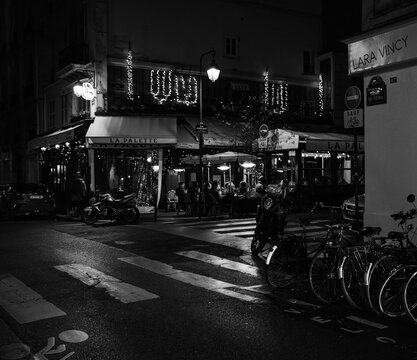 PARIS, FRANCE - DECEMBER 2, 2018: Unrecognizable people have a drink at evening at famous La Palette cafe terrace. It was frequented by Cezanne, Picasso, Braque,  Jacques Chirac. Black white photo.