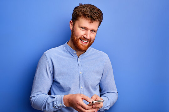 open-minded male is chatting with friend on smartphone, typing message, wearing blue formal shirt, smiling. isolated on blue background