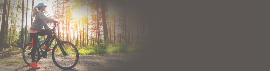 Woman riding a mountain bicycle along path at the forest. Long banner. Fotobehang