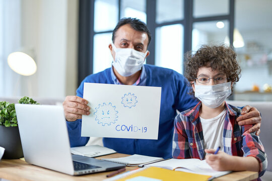 Safety. Middle aged hispanic father wearing mask sitting at the desk together with his son school boy and holding Covid 19 drawing during remote studying at home