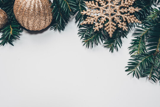Christmas background with spruce branches and golden glitter baubles and snowflake or stars decorations all laid on white background. Copy space with decorations on top.