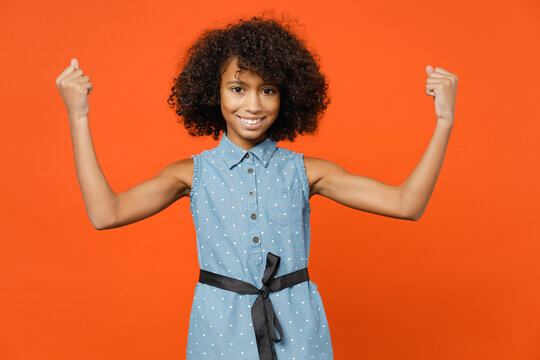 Smiling strong little african american kid girl 12-13 years old in denim dress showing biceps muscles isolated on bright orange color background children studio portrait. Childhood lifestyle concept.