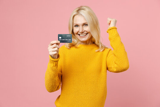 Happy elderly gray-haired blonde woman lady 40s 50s years old wearing yellow basic sweater standing hold credit bank card doing winner gesture isolated on pastel pink color background studio portrait.