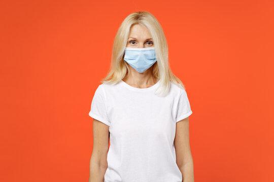 Elderly gray-haired blonde woman lady 40s 50s in white basic t-shirt sterile face mask to safe from coronavirus virus covid-19 during pandemic quarantine isolated on orange background studio portrait.