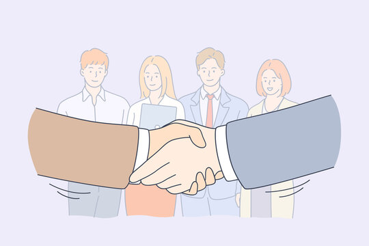 Handshake, partnership, business cooperation concept. Group of smiling young business workers colleagues standing and looking at shaking hands of head managers meaning collaboration in office