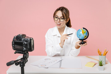 Funny woman tutor teacher in shirt glasses sit at desk hold Earth world globe conducting online...