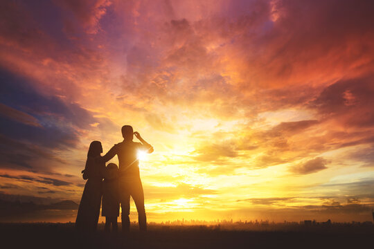 Silhouette of happy family look at modern city