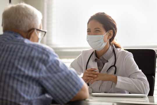 Smiling female doctor in facemask and white uniform talk consult mature male patient at consultation in clinic. Woman GP in facial mask have meeting with elderly client. Healthcare, covid-19 concept.