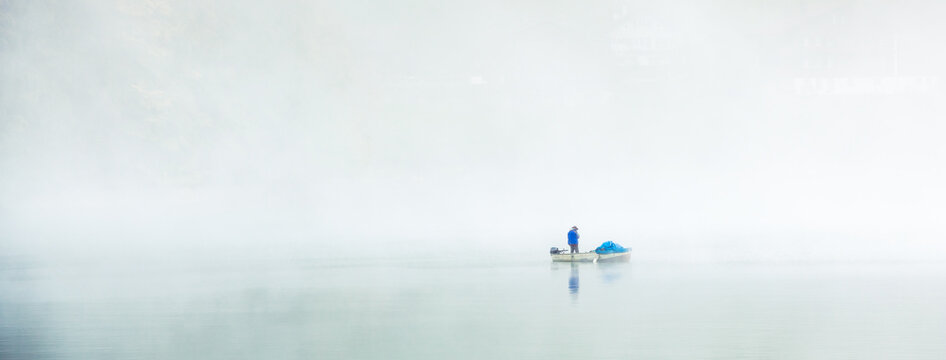 the lonely fisher in the mist, early morning a fisher man wit his boat  surrounded by fog, and the reflection in the water where you can only see the silhouette