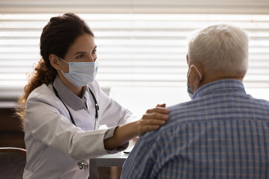 Caring female nurse in medical facemask touch calm support elderly male patient in hospital. Supportive woman doctor in facial mask show empathy comfort mature man in clinic. Healthcare concept.