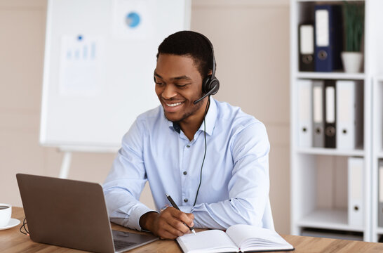 Cheerful black guy crisis manager working in front of laptop