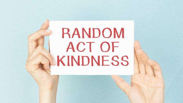 RANDOM ACT OF KINDNESS message on a yellow card hold by a business woman, business concept image with soft focus background