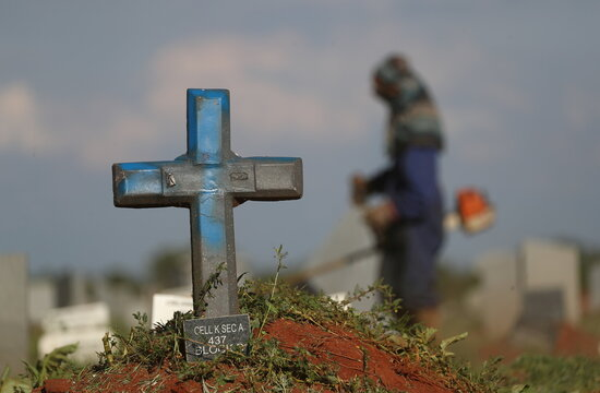 A cross marking a grave site is seen while a municipality worker cuts grass, as South Africa experiences a new variant of the coronavirus that is driving a second wave of infections