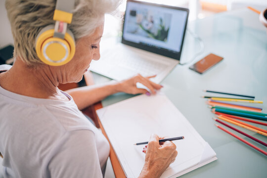 Woman drawing whilst taking online art class