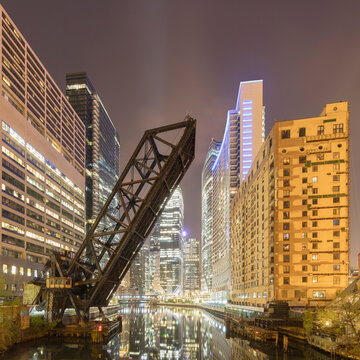 Bridge over river by buildings in city at night, Chicago, USA