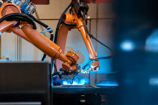 Orange color robotic arms manufacturing in industrial factory