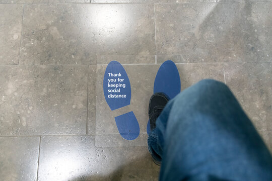 Woman stepping on floor sticker written Thank You For Keeping Social Distance on it