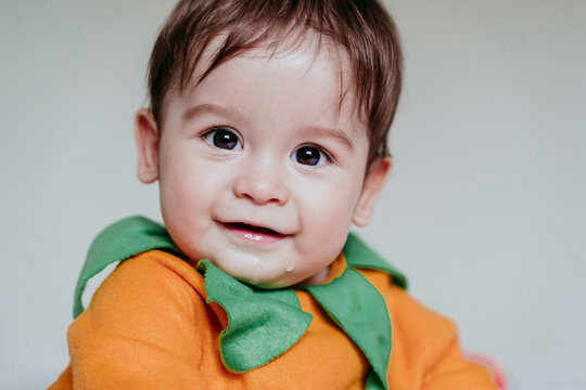 Smiling baby boy wearing halloween costume while sitting at home