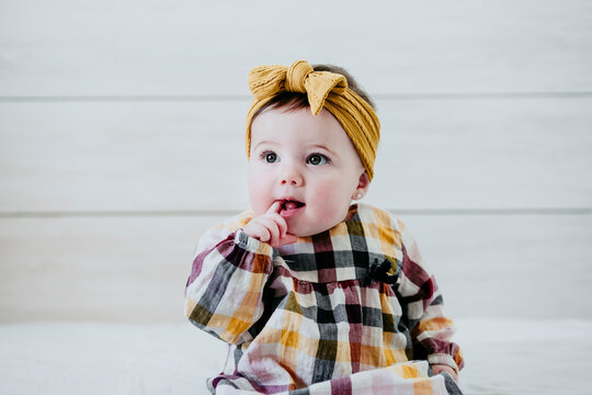 Baby girl with finger in mouth sitting on bed at home