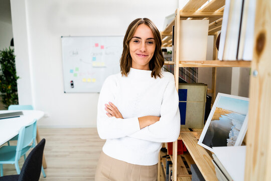 Smiling confident businesswoman standing with arms crossed at office