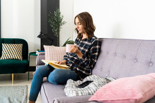 Young woman with coffee cup reading book while sitting on sofa at home