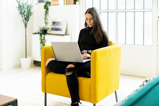 Young woman using laptop for blogging while sitting on chair at home