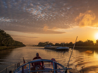 Man sailing boat along Juliana Canal at sunrise Fotobehang