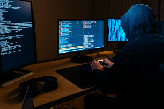 Hacker wearing hoodie working on computer while sitting at office