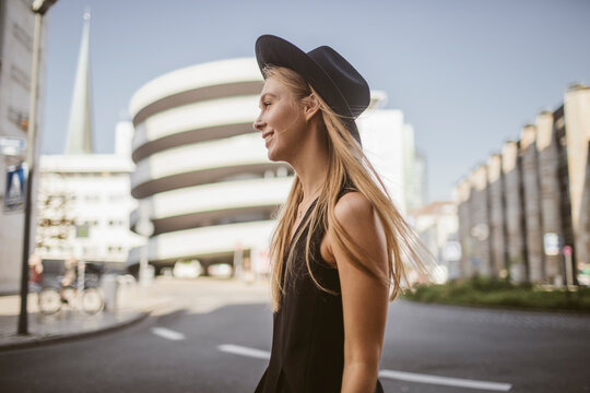 Smiling woman looking away while standing on street in city