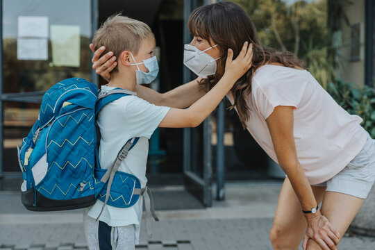Mother and son wearing protective mask standing face to face in front of school building