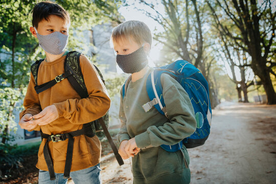 Brothers wearing protective face mask while walking in public park on sunny day