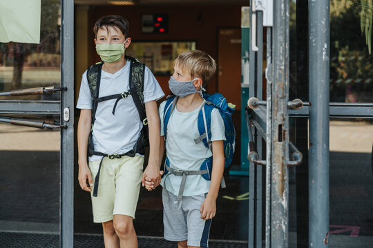 Brothers wearing protective face mask holding hands coming out of school building
