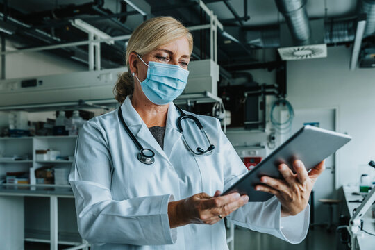 Scientist wearing face mask using digital tablet while standing at laboratory