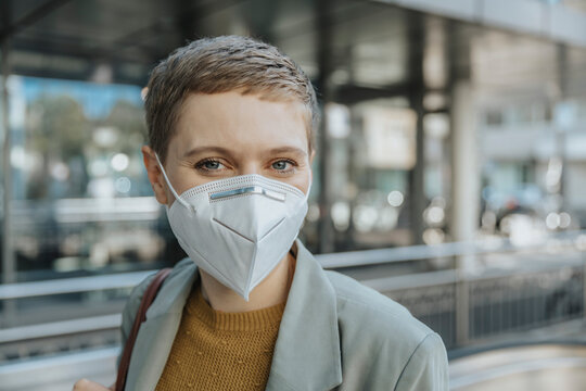 Woman wearing protective face mask standing in city
