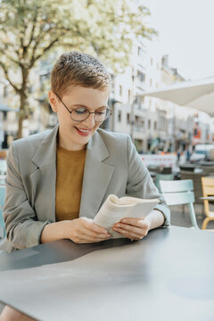 Smiling woman reading book sitting in sidewalk cafe on sunny day
