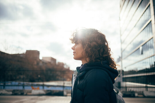 Mid adult woman looking away while standing by road at city