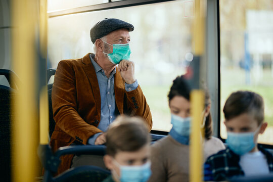 Pensive senior man wearing a face mask while commuting by bus.