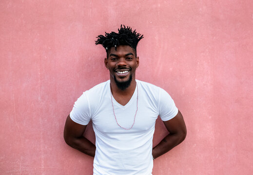 Smiling mid adult man wearing white t-shirt while standing against wall