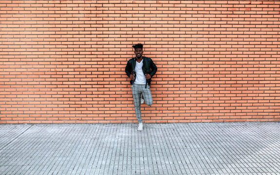Mid adult man wearing leather jacket standing against brick wall