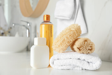 Wall Mural - Natural loofah sponges, towel and cosmetic products on table in bathroom