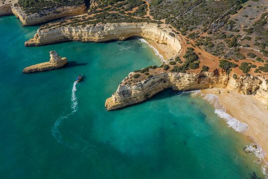 Drone view ofÔøΩtourboatÔøΩsailing by Praia do Pontal and Praia da Morena beaches