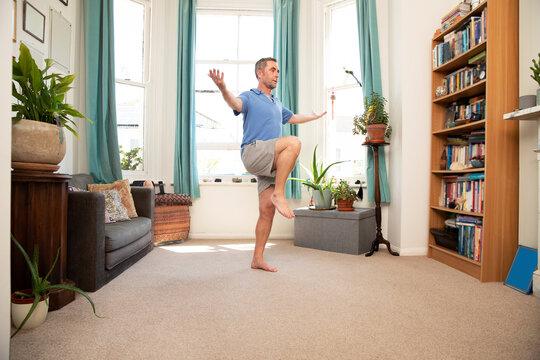 Mature man balancing on leg while standing at home